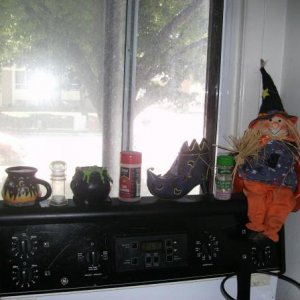 The top of my stove, with two cauldron candles, a witch boot, and my witchy-poo doll.