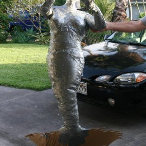 Fiijee Mermaid: cardboard provides the tail/fin at her bottom, a dorsel fin and wrist fins will soon follow, also cardboard. Layers of paper mache wil
