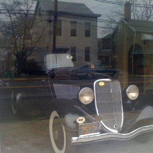 It has old cars and hot rods on the bottom floor behind glass windows...