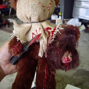 This is the knife bear, wearing a burlap mask, holding a knife and a decapitated doll head.