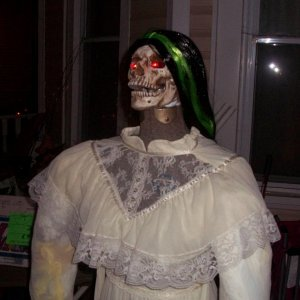 Improvised undead bride.  Used neighbor Cindy's dresing dummy and old wedding dress.  Plastic skull, $3 wig and mini leds complete the effect.